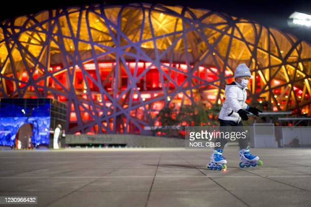 Boy skates in front of the Birds Nest stadium, the venue for opening and closing ceremonies at the 2022 Winter Olympics, in Beijing on February 4 a...