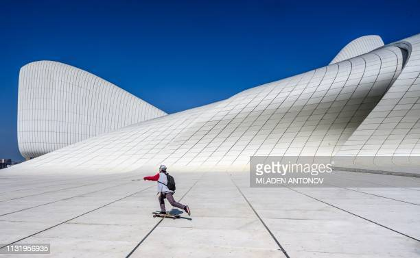 A boy skates in front of the Heydar Aliyev Center in Baku on March 22 2019 The building was designed by IraqiBritish architect Zaha Hadid and is...