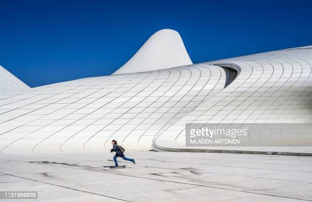 TOPSHOT A boy skates in front of the Heydar Aliyev Center in Baku on March 22 2019 The building was designed by IraqiBritish architect Zaha Hadid and...
