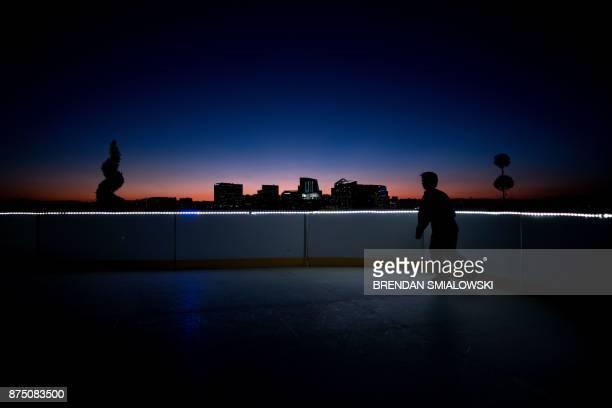 A boy skates on synthetic ice atop the Watergate Hotel November 16 2017 in Washington DC / AFP PHOTO / Brendan Smialowski