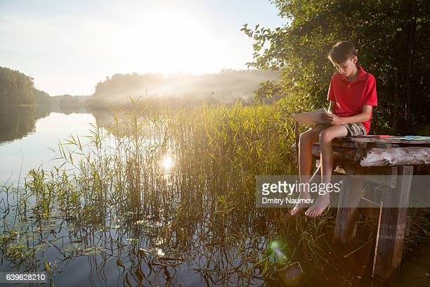 Boy sketching a summer landscape with a forest lake