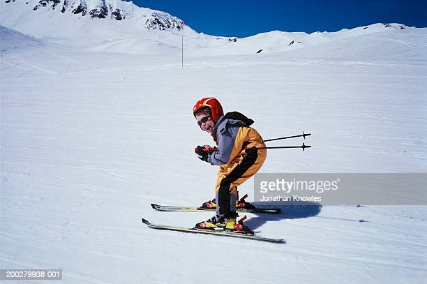 Boy (6-8) skiing, mouth open, side view