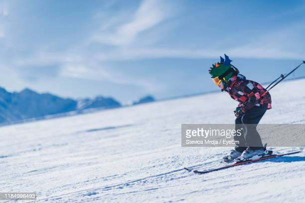 boy skiing on snowcapped mountain - skiing stock pictures, royalty-free photos & images