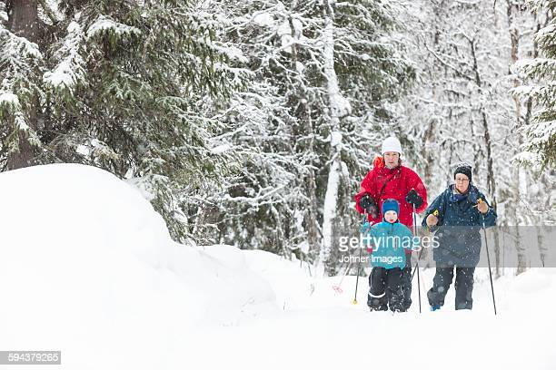 Boy skiing with parents