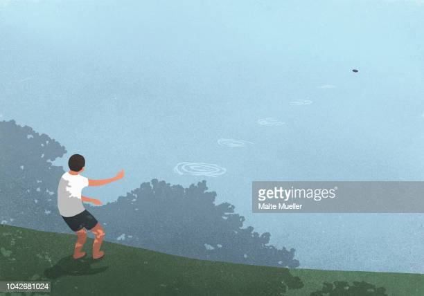 boy skipping stones at blue lake - illustration stock pictures, royalty-free photos & images