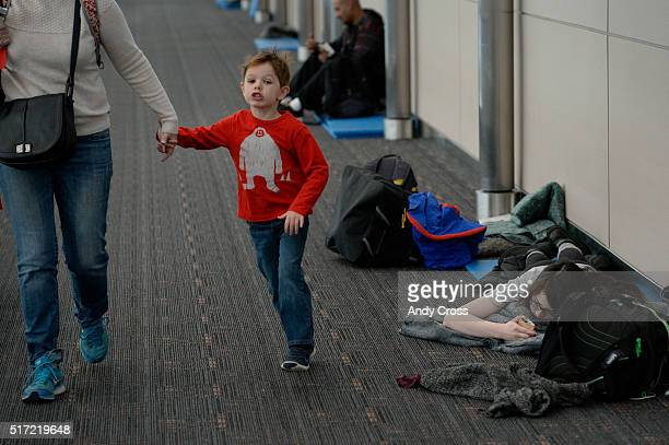 A boy skips past airline passenger Bailey Fox while she checks her messages on her phone waking up on the floor at Denver International Airport March...
