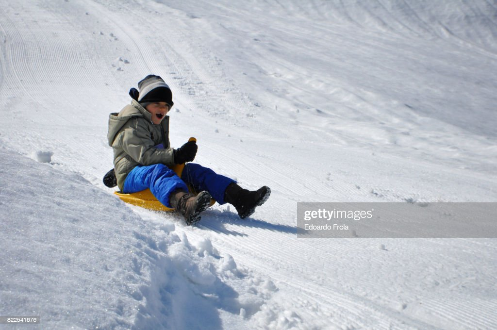 Boy sledging on snow covered slope : Stock Photo