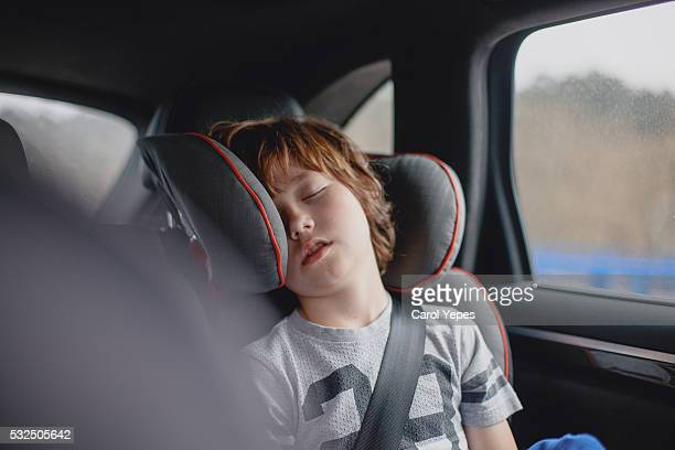 Boy sleeping in back seat of car