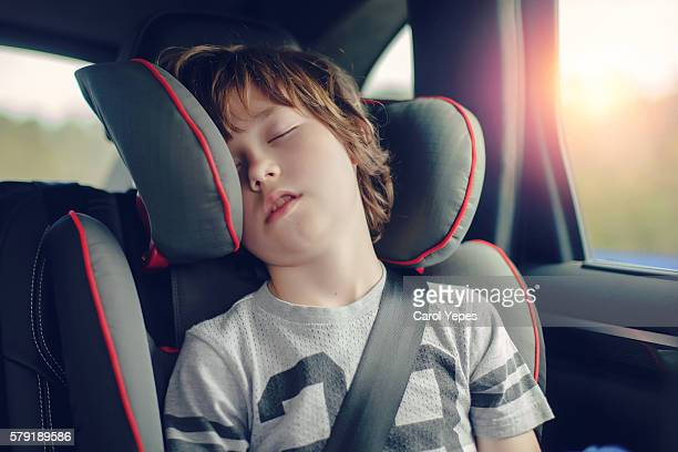 Boy sleeping in back seat of car