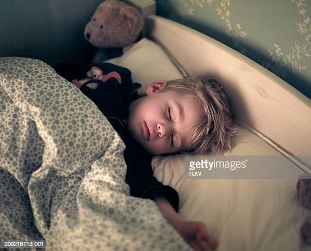 Boy (2-4) sleeping in bed