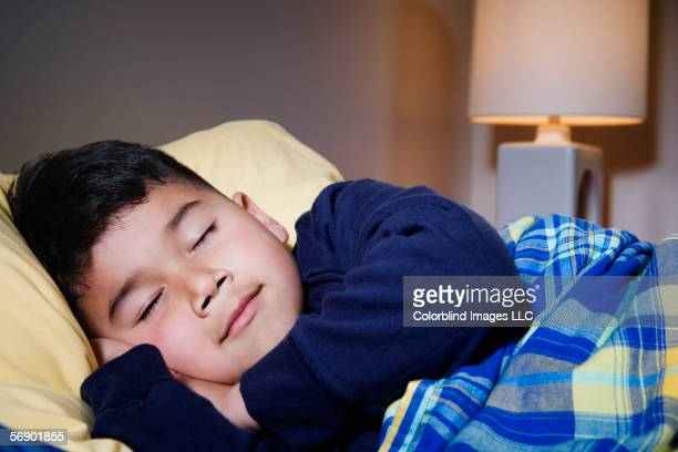Boy sleeping in bed with light on