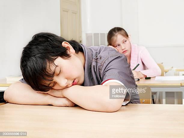 Boy (10-11) sleeping in classroom