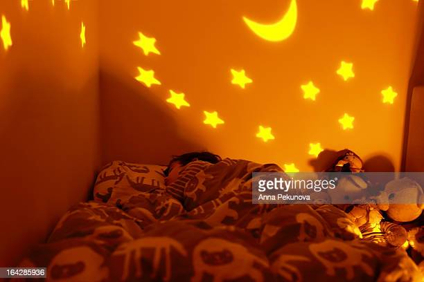 Boy sleeping in his bed at night