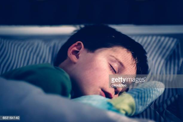 Boy sleeping in his bed.