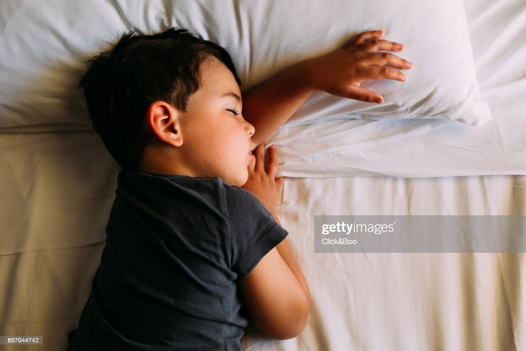Boy sleeping in his bed : Stock Photo