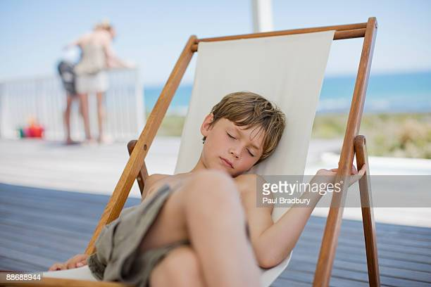 Boy sleeping in lounge chair on deck