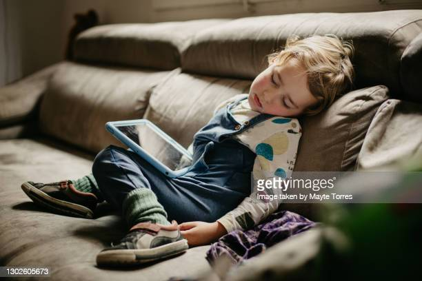 boy sleeping in the sofa with the tablet, from the side - day 4 stockfoto's en -beelden