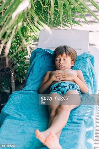 Boy sleeping on a sun lounger on beach