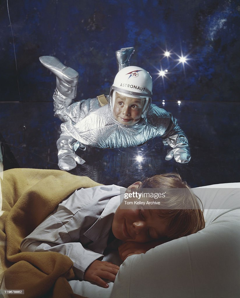 Boy sleeping on bed dreaming of astronaut : Stock Photo