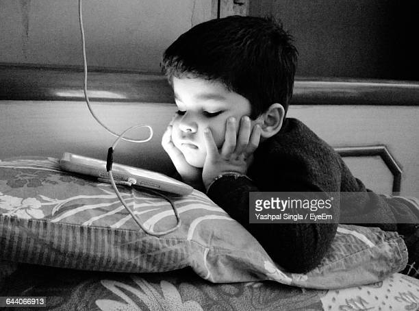 Boy Sleeping On Bed With Mobile Phone At Home