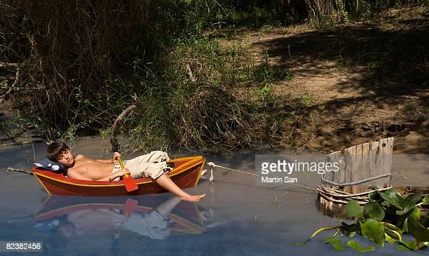 Boy sleeping on canoe floating in water