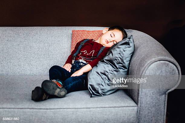Boy sleeping on couch with a gray cushion