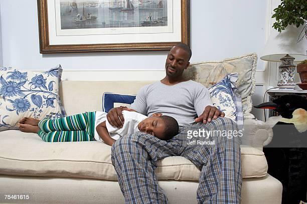Boy (6-7) sleeping on father's lap