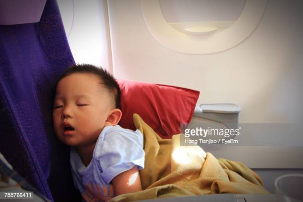 Boy Sleeping On Seat While Traveling In Airplane