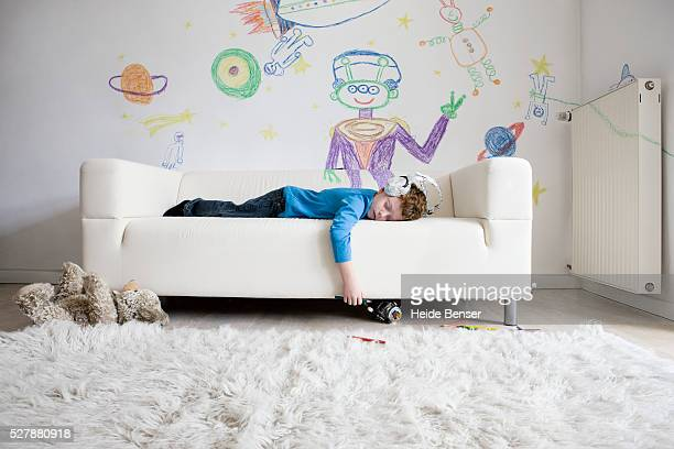Boy (7-9) sleeping on sofa