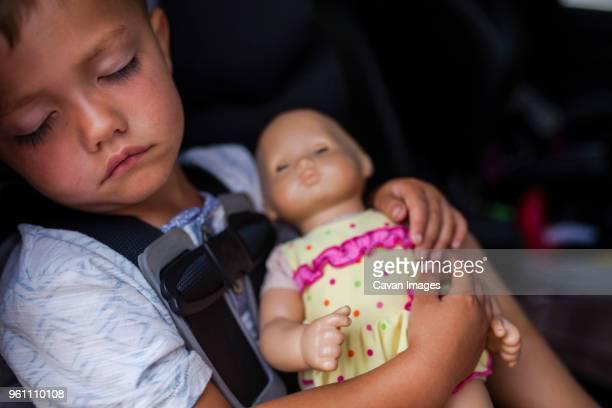 boy sleeping with doll in car - puppe stock-fotos und bilder