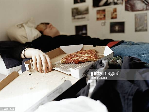 boy sleeping with pizza on bed - laziness stock pictures, royalty-free photos & images
