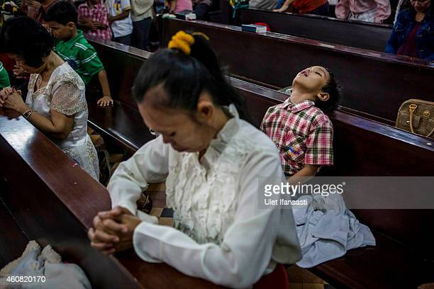 A boy sleeps during Christmas Eve mass at Hati Kudus church on December 24 2014 in Banda Aceh Indonesia Aceh is the only province to implement Sharia...