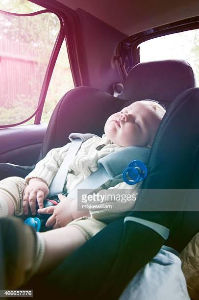 Boy sleeps in baby car seat on a road trip