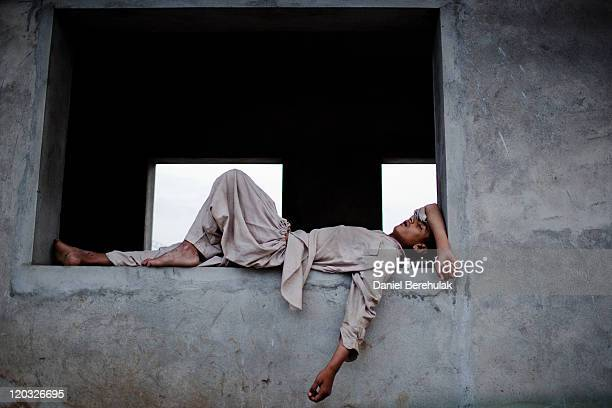 A boy sleeps on a wall at a bus station during 'Iftar' when Muslims break their fast on the third day of the holy month of Ramadan on August 4 2011...