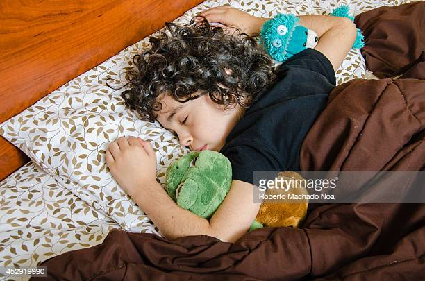 Boy sleeps over his belly quietly with his favorite stuffed toy