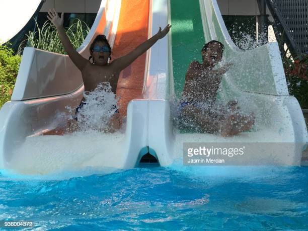 boy sliding and diving into pool - one boy only stock pictures, royalty-free photos & images