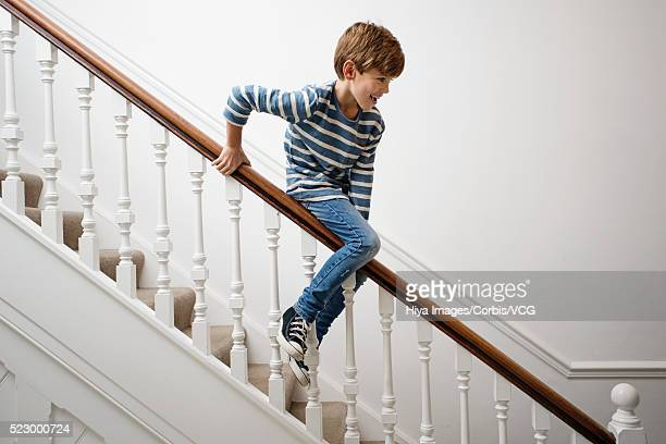 boy sliding down bannister - sliding stock pictures, royalty-free photos & images