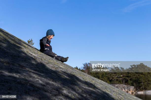 Boy sliding down hill