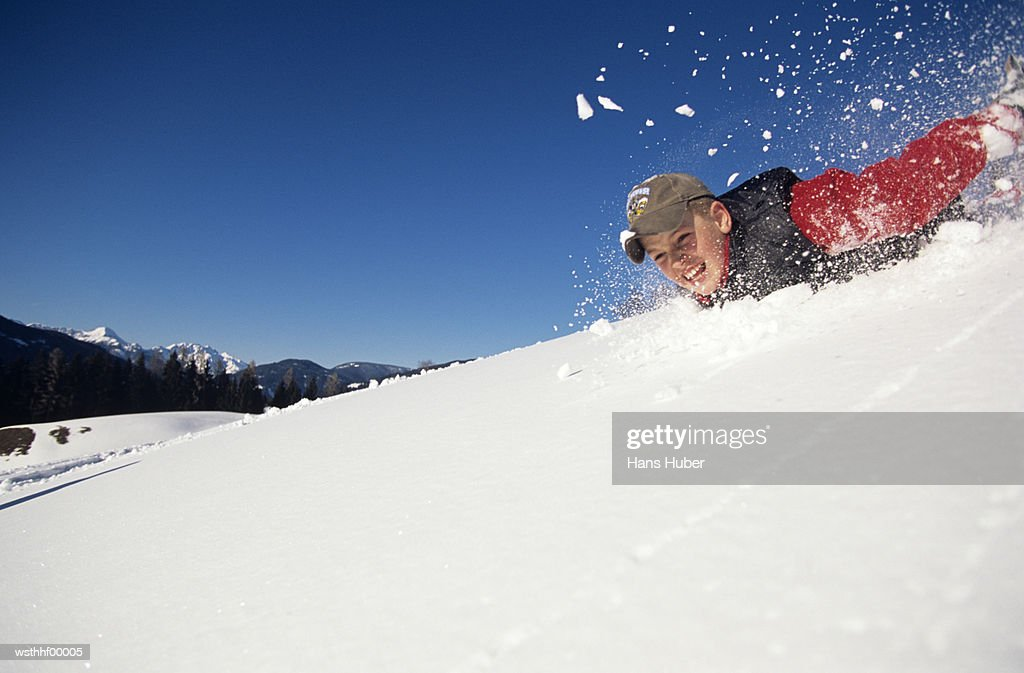 Boy sliding down snow slope : Stockfoto