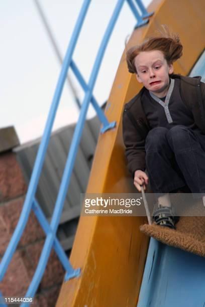 boy sliding down steep slide - catherine macbride stock-fotos und bilder