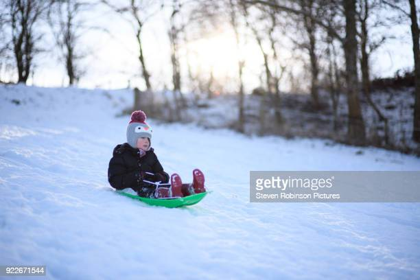 Boy sliding downhill on Sledge in the Snow