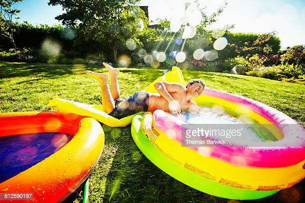 Boy sliding into inflatable pool from water slide
