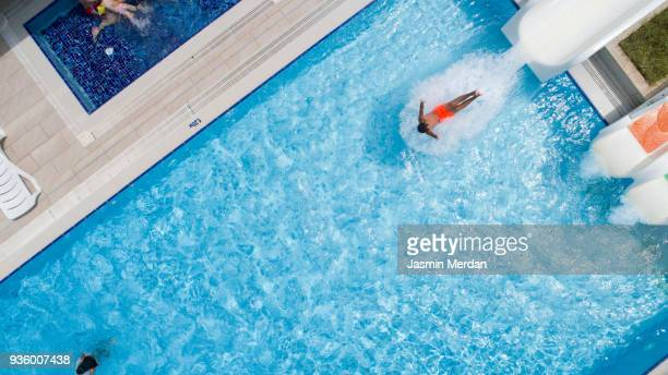 Boy sliding into pool