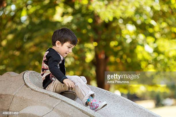 Boy sliding on stone slide