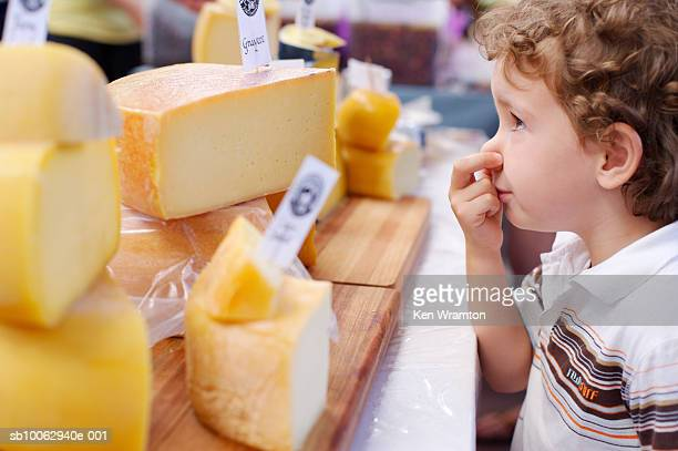 Boy (2-3) smelling cheese at stall, profile
