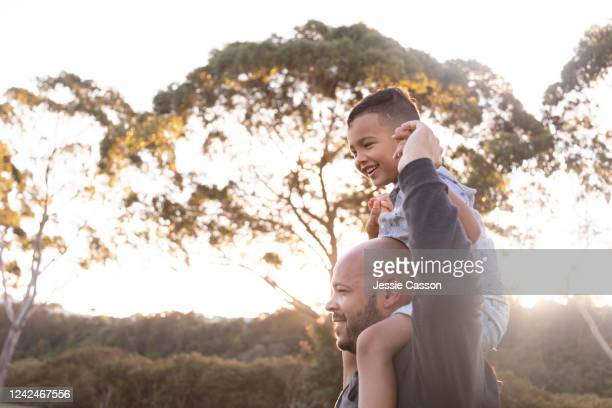 boy smiles as father holds him on his shoulders - light natural phenomenon stock pictures, royalty-free photos & images