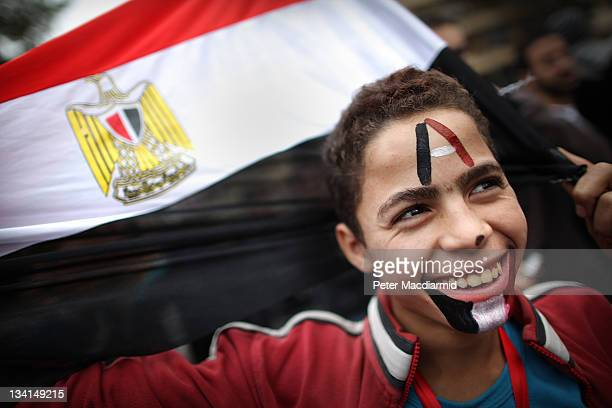 A boy smiles as he holds an Egyptian flag in Tahrir Square on November 27 2011 in Cairo Egypt Protestors are continuing to occupy Tahrir Square ahead...
