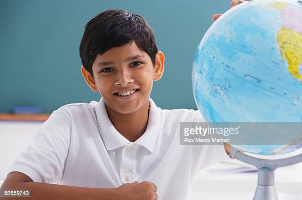 boy smiles at camera with globe - world at your fingertips stock pictures, royalty-free photos & images