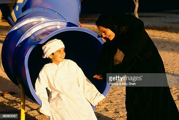 A boy smiles at his mother while sitting in the tube in the park.