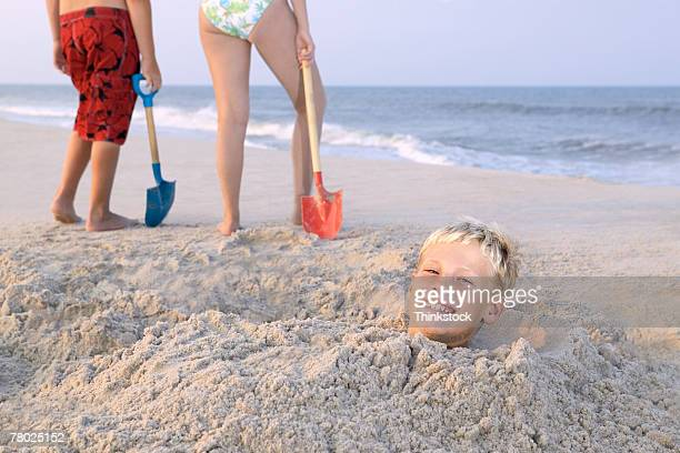 a boy smiles to the viewer while buried in the sand, and two kids stand with shovels in the background - enterrar imagens e fotografias de stock